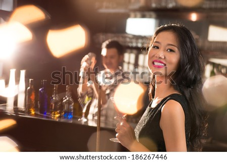 Portrait of smiling Vietnamese brunette in the bar - stock photo