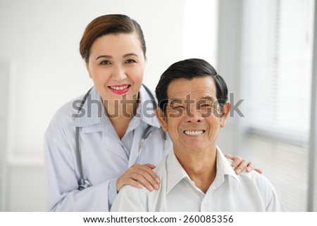 Portrait of smiling Vietnamese doctor and her retired patient - stock photo