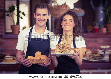 Portrait of smiling waiter and waitress holding bread bun at coffee shop - stock photo