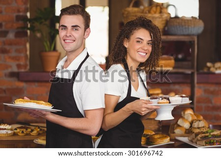 Portrait of smiling waiter and waitress holding plates with treat at coffee shop