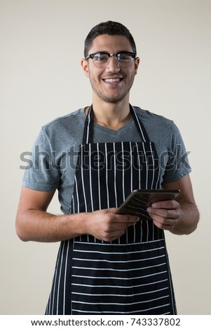 Portrait of smiling waiter standing with a digital tablet
