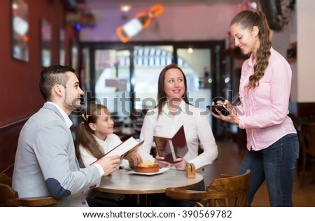 Portrait of smiling waitress and happy family with child reading menu. Focus on the man - stock photo