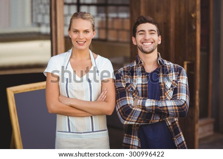 Portrait of smiling waitress and her colleague with arms crossed at coffee shop - stock photo