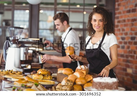 Portrait of smiling waitress holding bread roll with tong at coffee shop