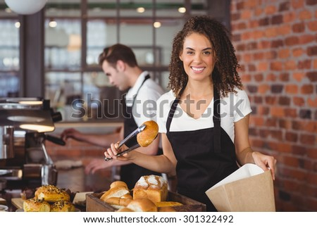 Portrait of smiling waitress putting bread roll in paper bag at coffee shop - stock photo