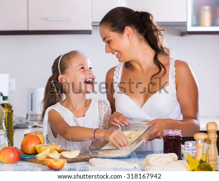 Portrait of smiling woman and child cooking apple strudel in kitchen - stock photo