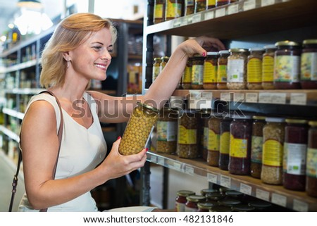 Portrait of smiling woman buying conserve peas in glass jar in grocery shop