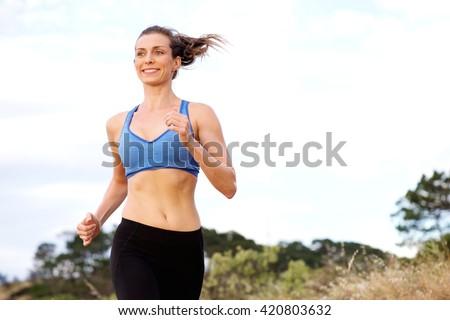 Portrait of smiling woman enjoying run outside  - stock photo