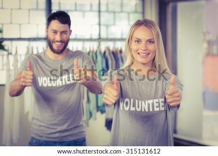 Portrait of smiling woman giving thumbs up while male colleague seen in background in office - stock photo