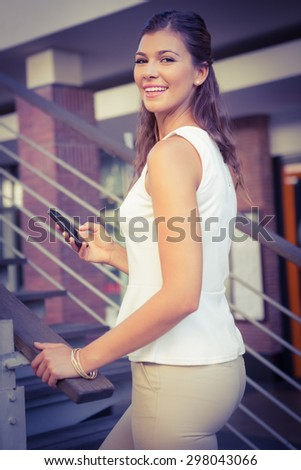 Portrait of smiling woman going upstairs while using her smartphone at the shopping mall