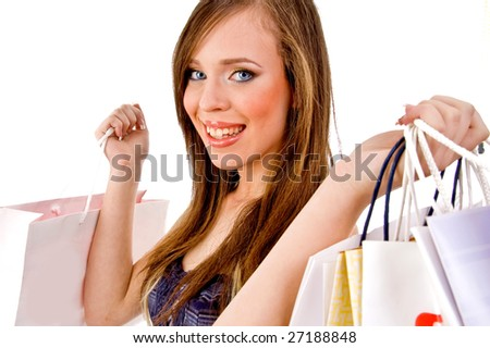 portrait of smiling woman holding bags against white background - stock photo