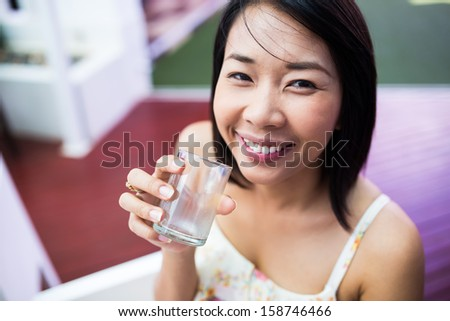 Portrait of smiling woman holding empty glass of water - stock photo