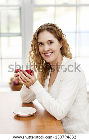 portrait of smiling woman holding red coffee cup sitting at table in home kitchen by window