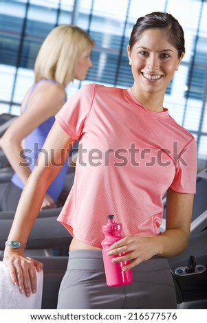 Portrait of smiling woman holding water bottle on treadmill in health club