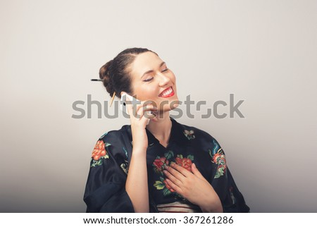 Portrait of smiling woman in kimono talking by phone  - stock photo