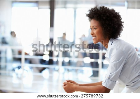 Portrait of smiling woman in office, side view - stock photo