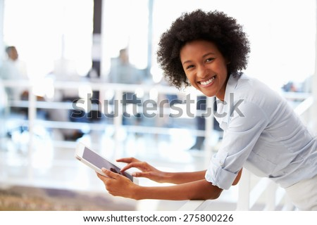 Portrait of smiling woman in office with tablet - stock photo