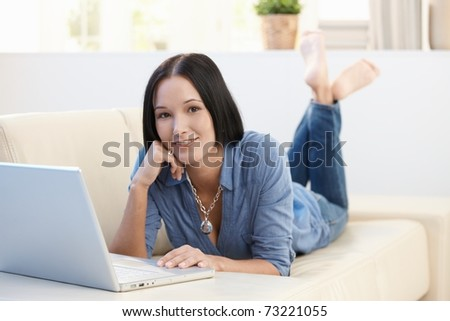 Portrait of smiling woman lying on sofa with laptop computer, looking at camera.? - stock photo