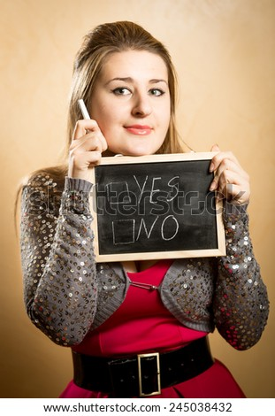 Portrait of smiling woman making decision on white chalkboard - stock photo