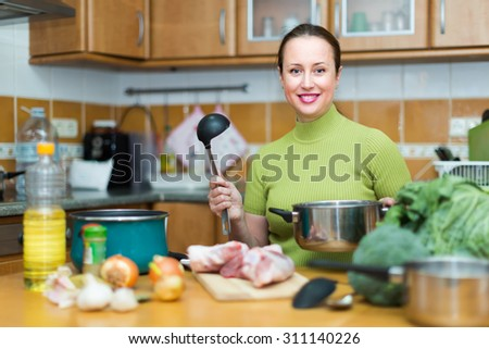 Portrait of smiling woman preparing dinner for family indoor - stock photo