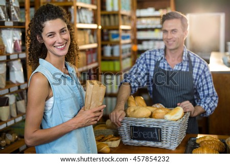 Portrait of smiling woman purchasing bread at bakery store in supermarket - stock photo
