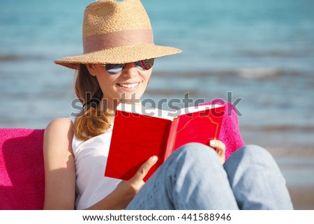 Portrait of smiling woman relaxing on the beach and reading a book while on summer vacation.