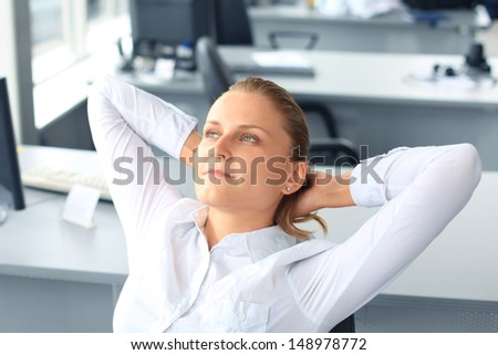 Portrait of smiling woman sitting and resting inside the office