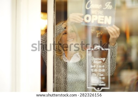 Portrait of smiling woman standing behind her clothing store shop window. Small business.  - stock photo