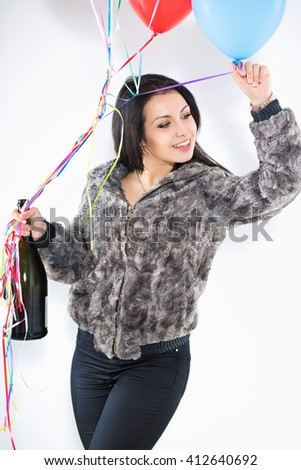 Portrait of smiling woman with a big bottle and balloons wearing furry jacket - stock photo