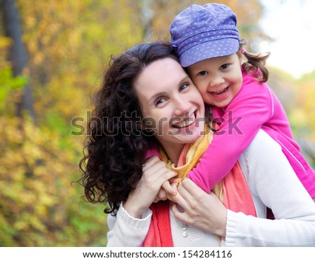Portrait of smiling woman with cute little girl in autumn park
