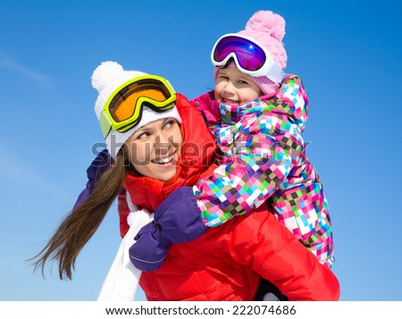 Portrait of smiling woman with cute little girl in wintertime - stock photo