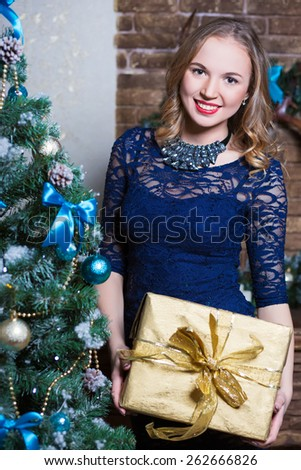 Portrait of smiling woman with gift box posing near the fir-tree - stock photo