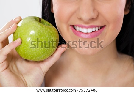 portrait of smiling woman with perfect teeth eating green apple
