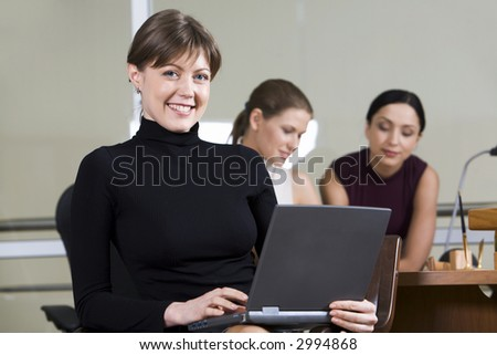 Portrait of smiling woman with the laptop on her knees sitting in the café and two girls on the background - stock photo