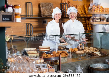 Portrait of smiling women at bakery display with pastry - stock photo