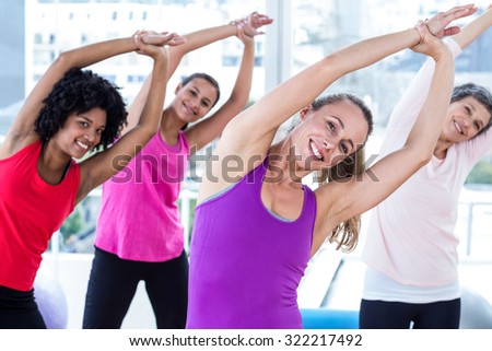 Portrait of smiling women exercising with arms raised in fitness studio