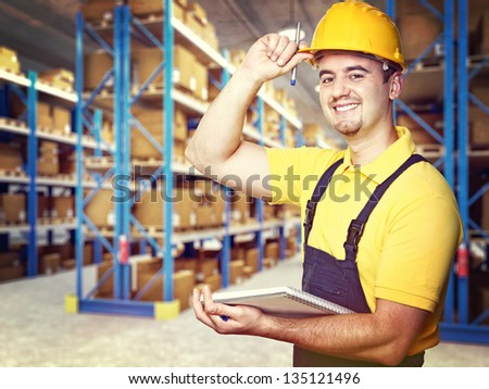 portrait of smiling worker in warehouse - stock photo