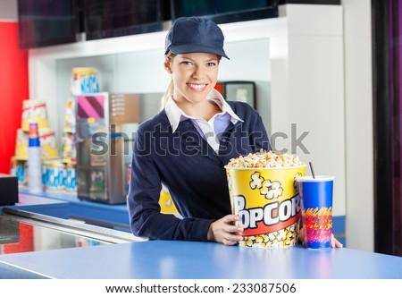 Portrait of smiling worker with popcorn bucket and drink at cinema concession counter - stock photo