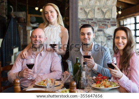 Portrait of smiling young adults having dinner in restaurant. Focus on young man - stock photo
