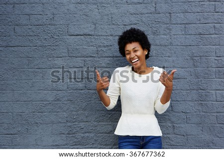 Portrait of smiling young african american woman gesturing thumbs up sign with both her hands against gray wall  - stock photo