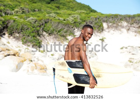 Portrait of smiling young african man with surfboard going for surfing at beach