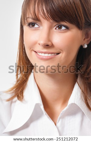 Portrait of smiling young attractive businesswoman looking up or thinking - stock photo