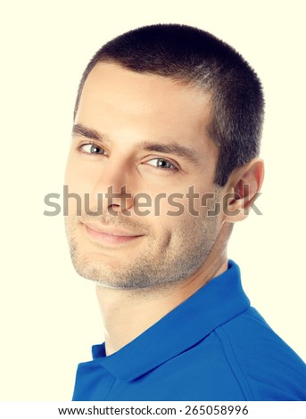 Portrait of smiling young attractive handsome man in blue casual t-shirt clothing, looking at camera - stock photo
