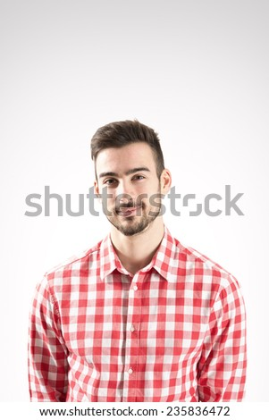 Portrait of smiling young bearded man looking at camera over gray background - stock photo