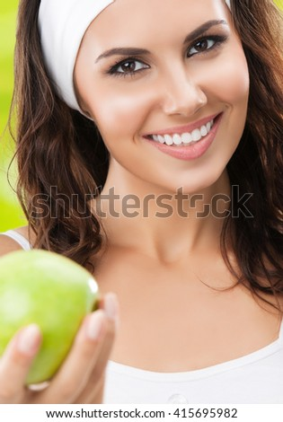 Portrait of smiling young beautiful brunette woman in fitness wear with apple, outdoors. Healthy lifestyle, beauty and dieting concept. - stock photo