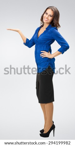 Portrait of smiling young beautiful businesswoman in business style clothing, showing something or blank copyspase for product or sign text - stock photo