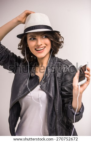 Portrait of smiling young beauty woman listening music in headphones on grey background. - stock photo