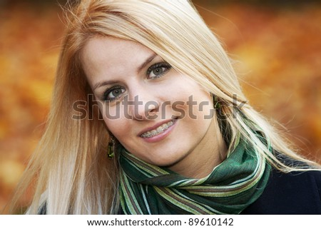 Portrait of smiling young blond woman over autumnal background - stock photo