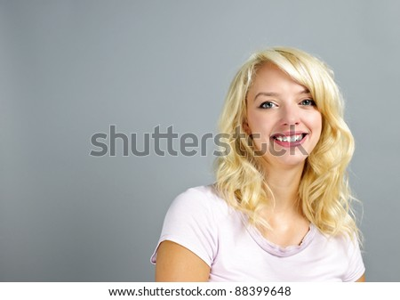 Portrait of smiling young blonde caucasian woman on grey background - stock photo