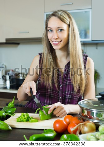 Portrait of smiling young blonde woman cooking with vegetables at kitchen